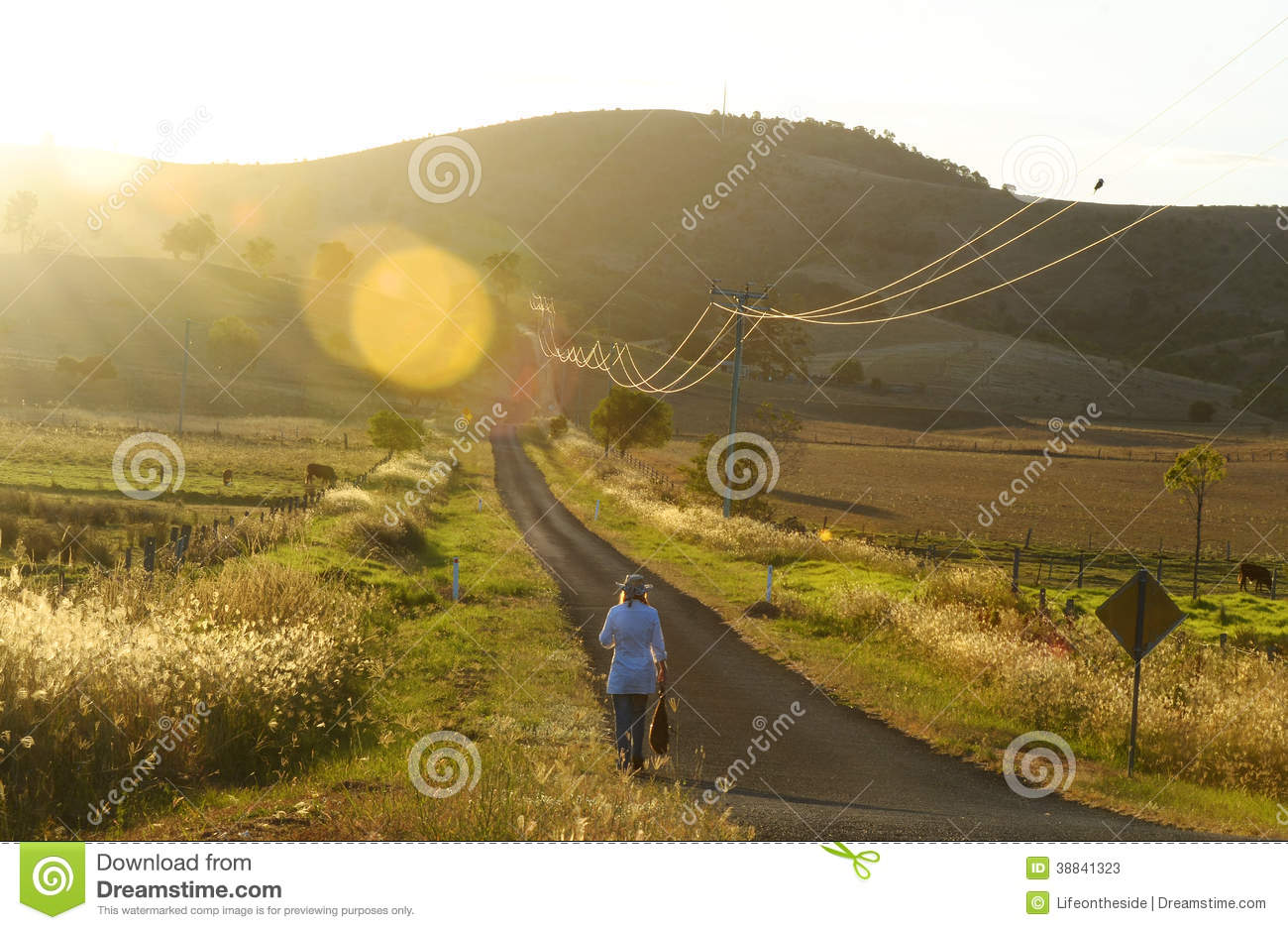 Woman walking long country road home sunset