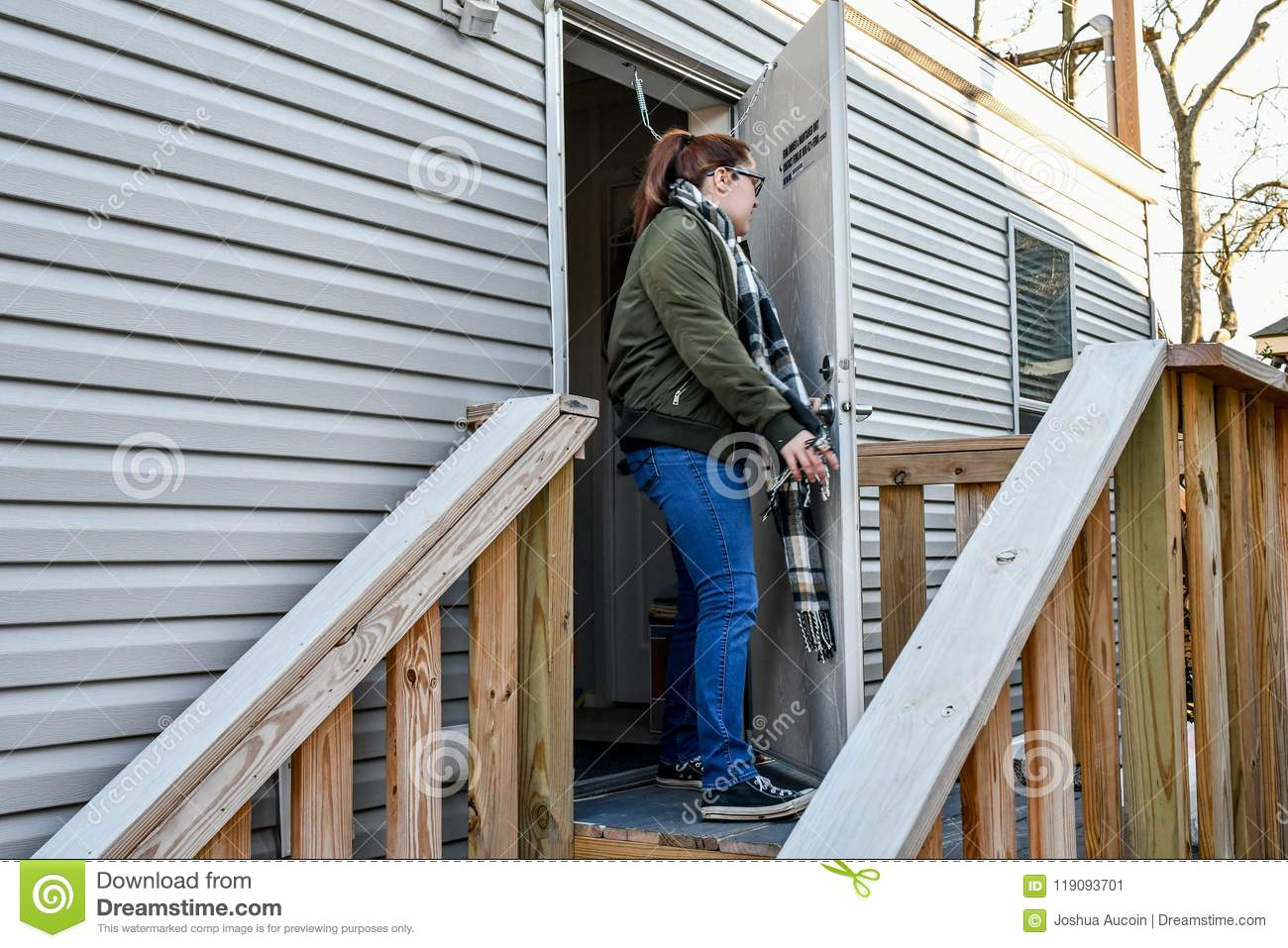 A woman walks out her front door to leave home.
