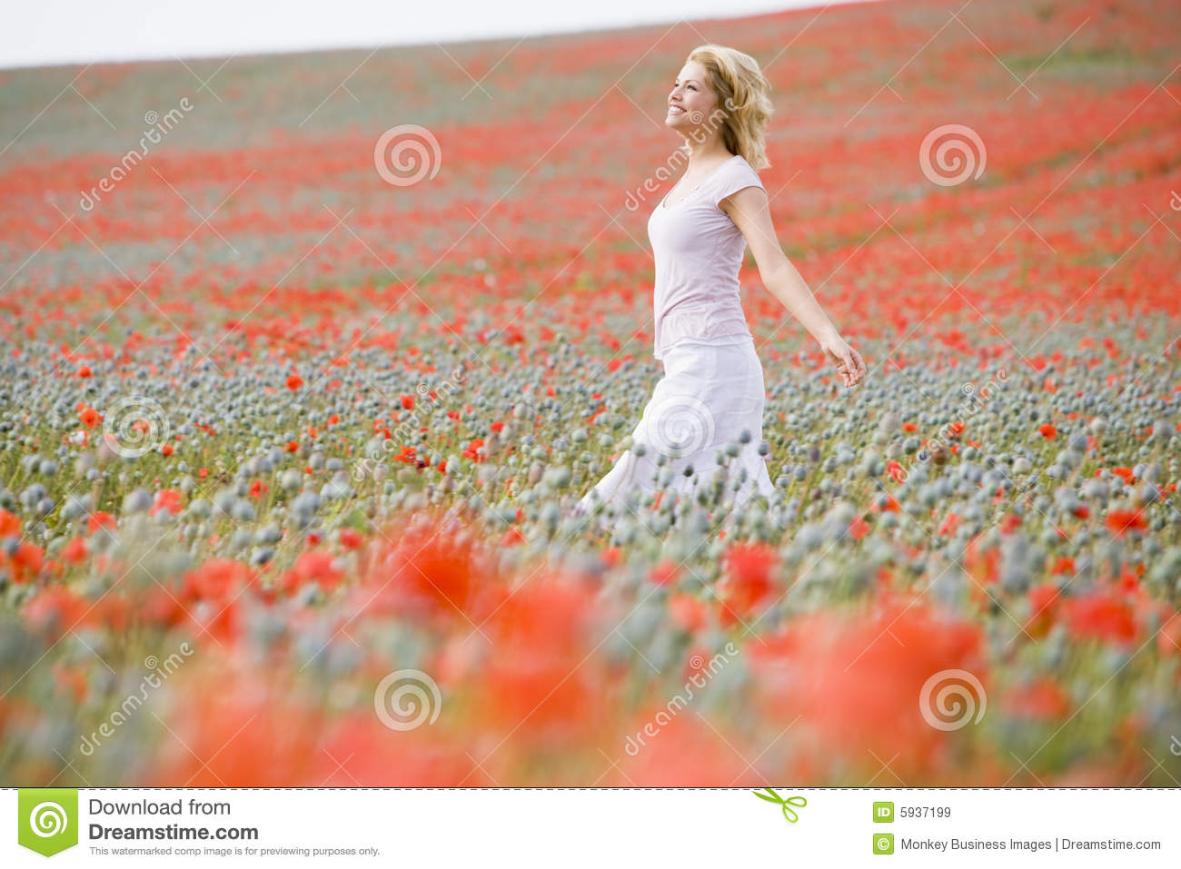 Woman walking in poppy field
