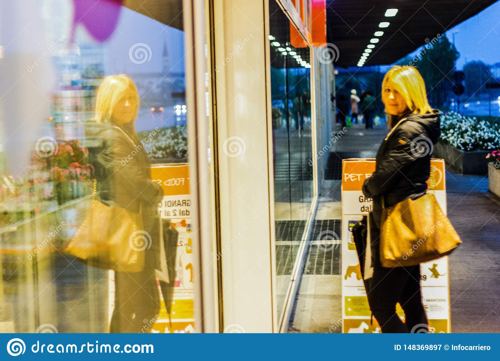 woman walking in the streets admiring shop windows intent on doing shopping