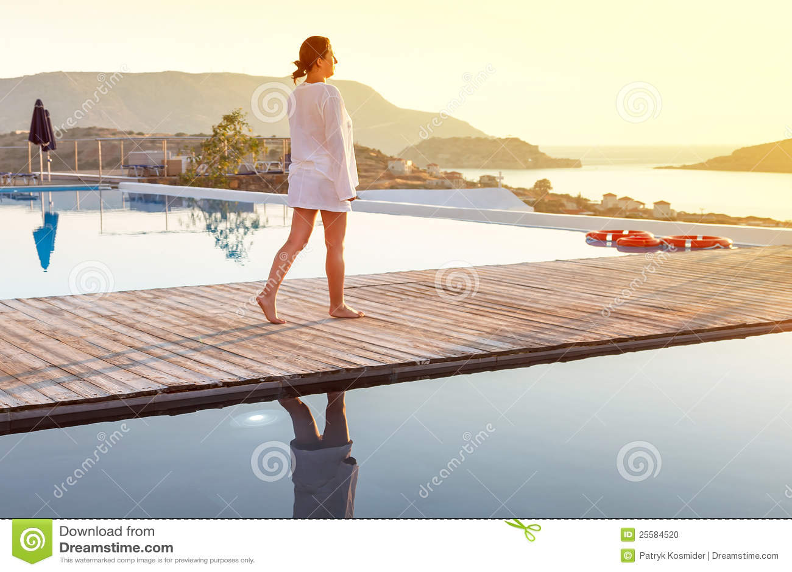 Woman walking at sunrise near swimming pool stock photo - Where is my nearest swimming pool ...