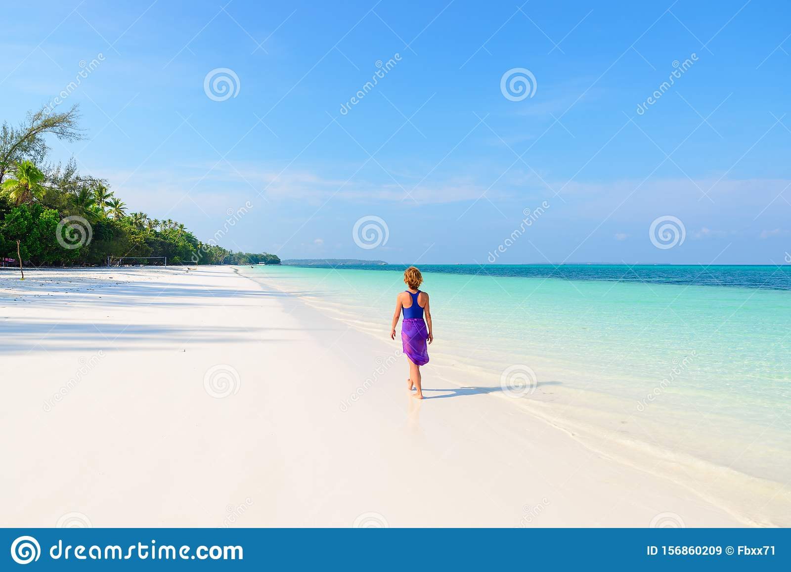 Woman walking on tropical beach. Rear view white sand beach turquoise trasparent water caribbean sea real people. Indonesia Kei