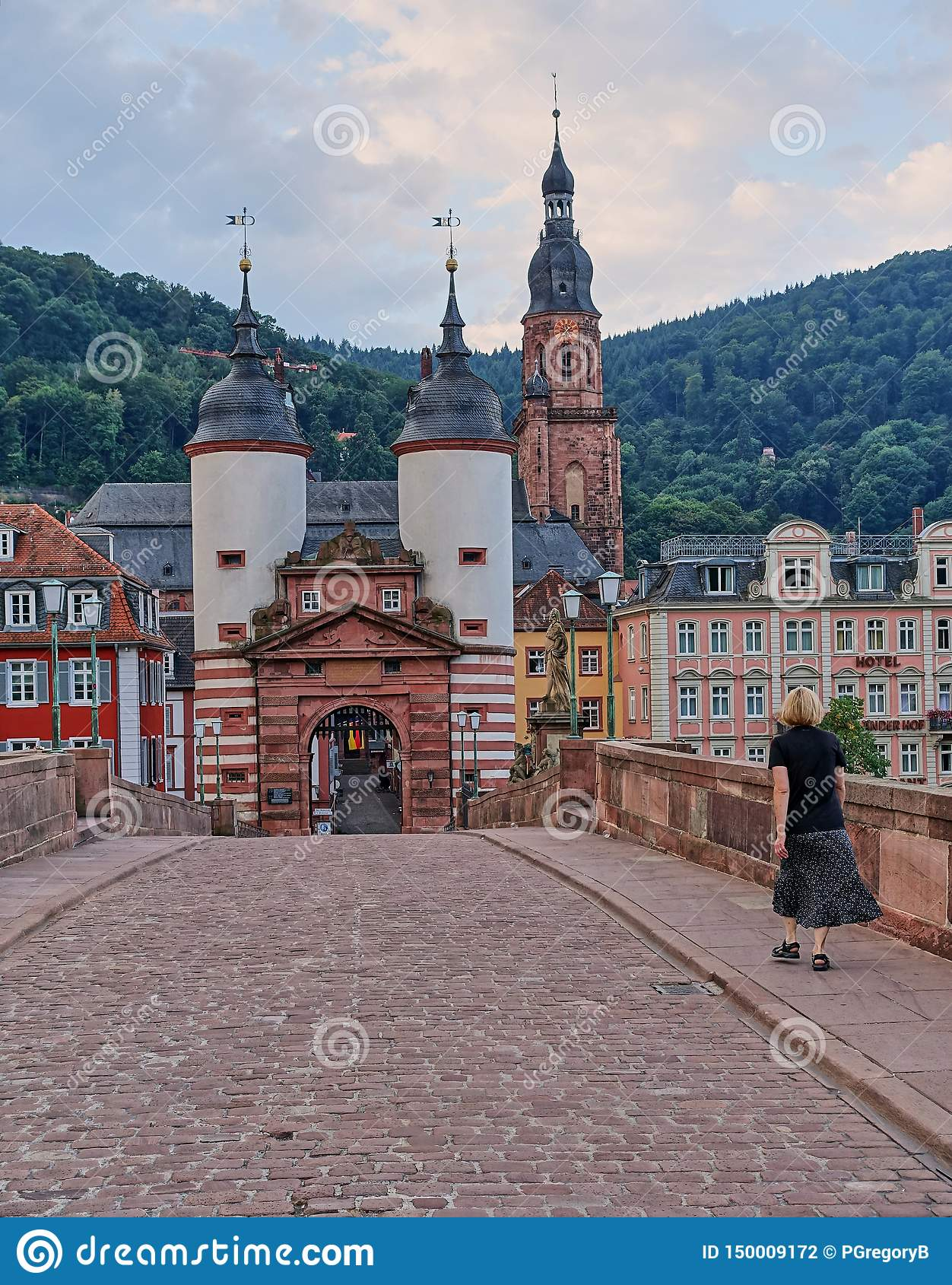 Woman Walks across Old Bridge in destination town of Heidelberg, Germany