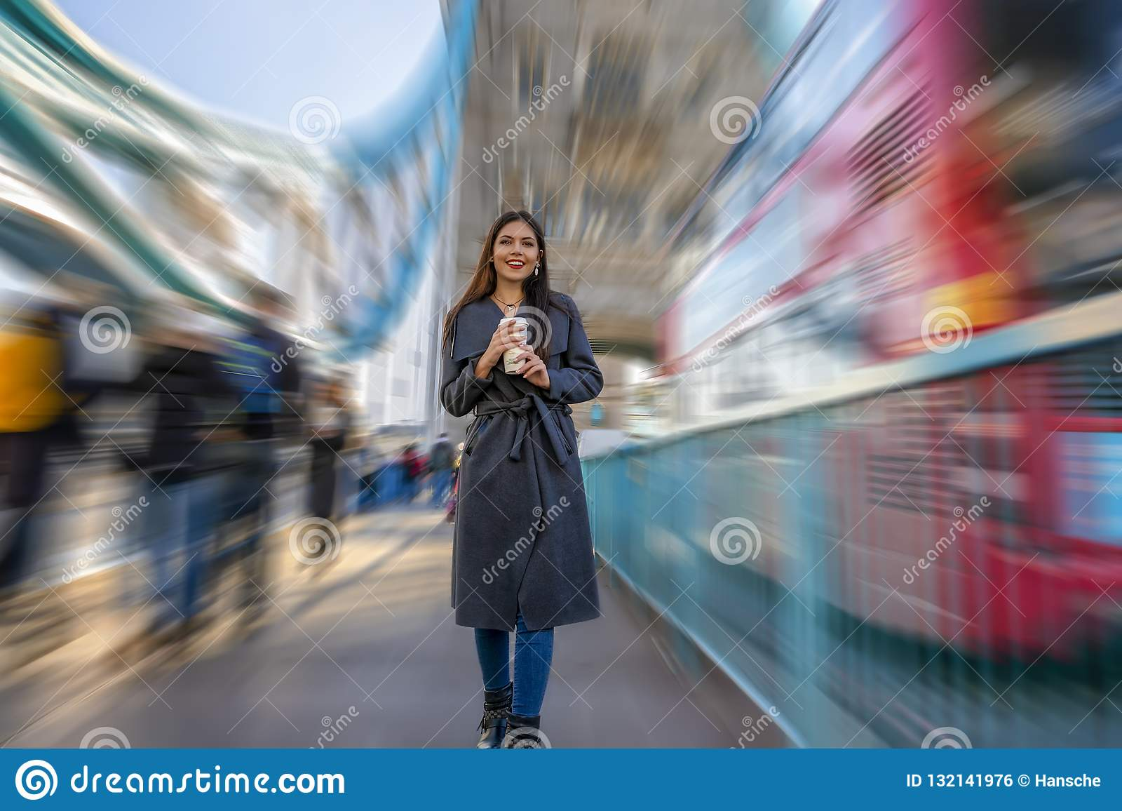 Woman walks down the Tower Bridge with a coffee in her hand