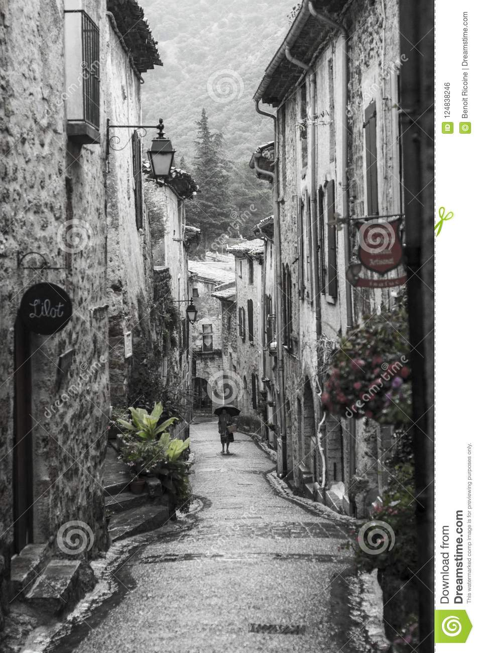 Woman walks by in a street of the medieval French village of Saint-Guilhem-le-Désert