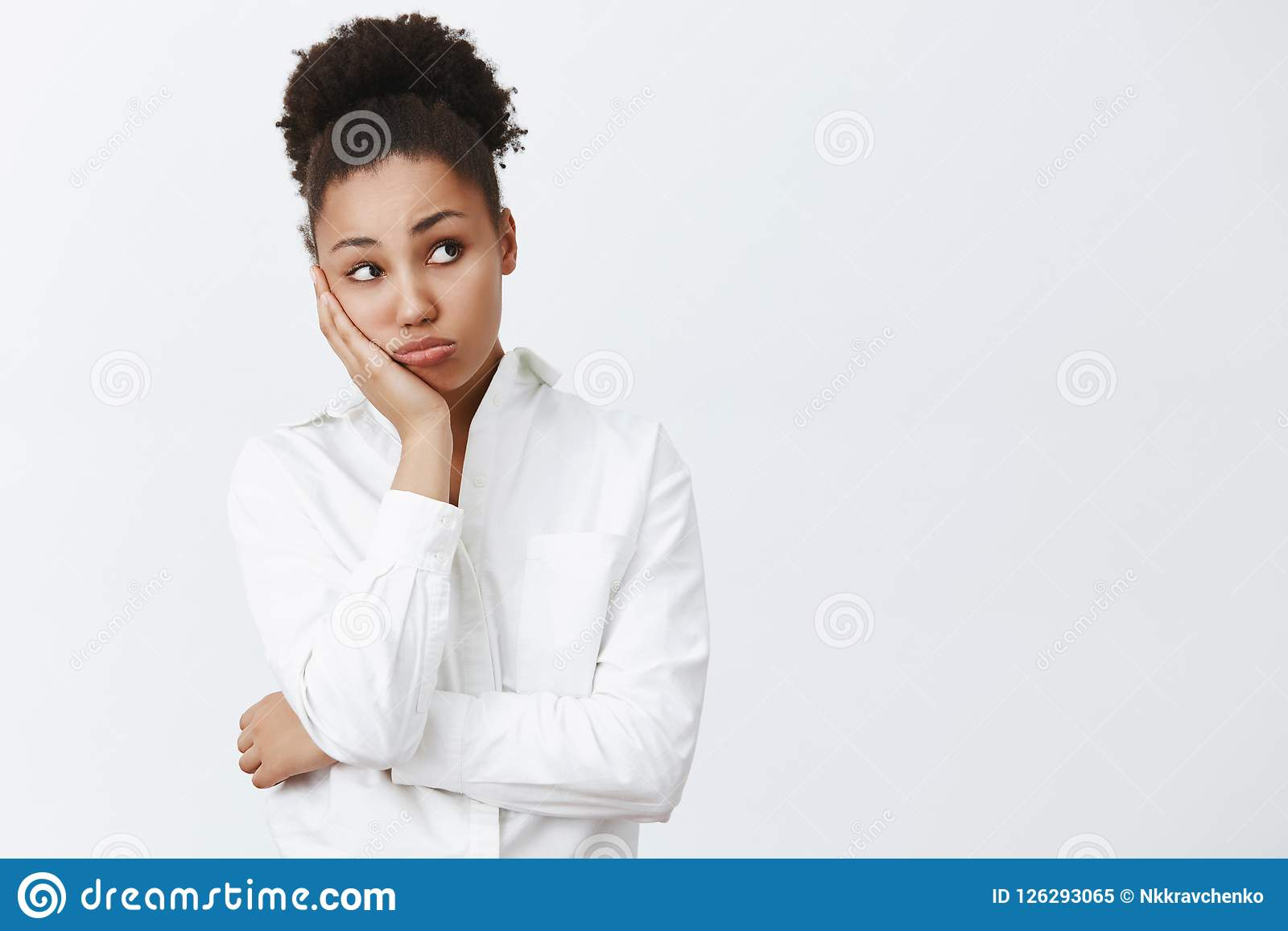 Woman wants go home, waiting clock ring to leave office. Portrait of dreamy tired and bored cute african-american female