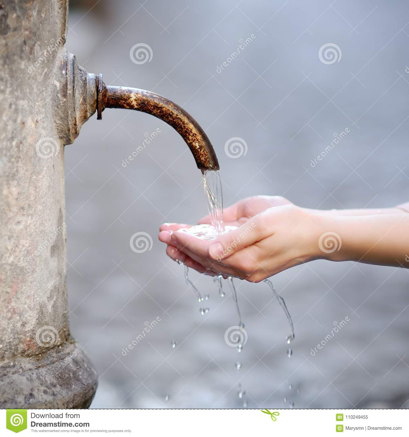 Woman washing hands in a city fountain in Rome, Italy