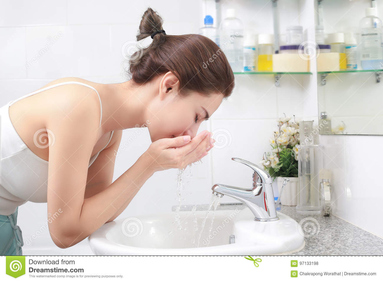Woman washing her face with water above bathroom sink.