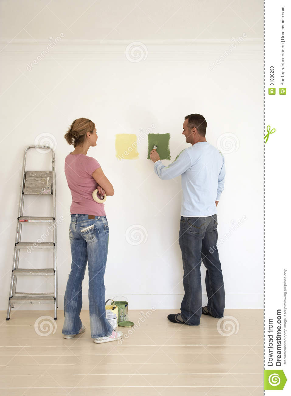 Woman Watch Man Testing Paint Colors On Wall Stock Photo