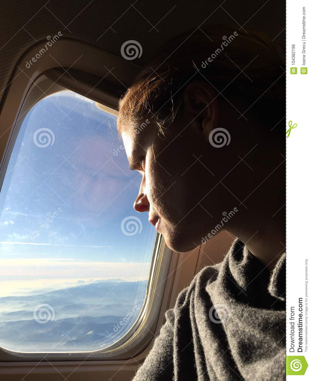 Woman watching out the windows of an airplane