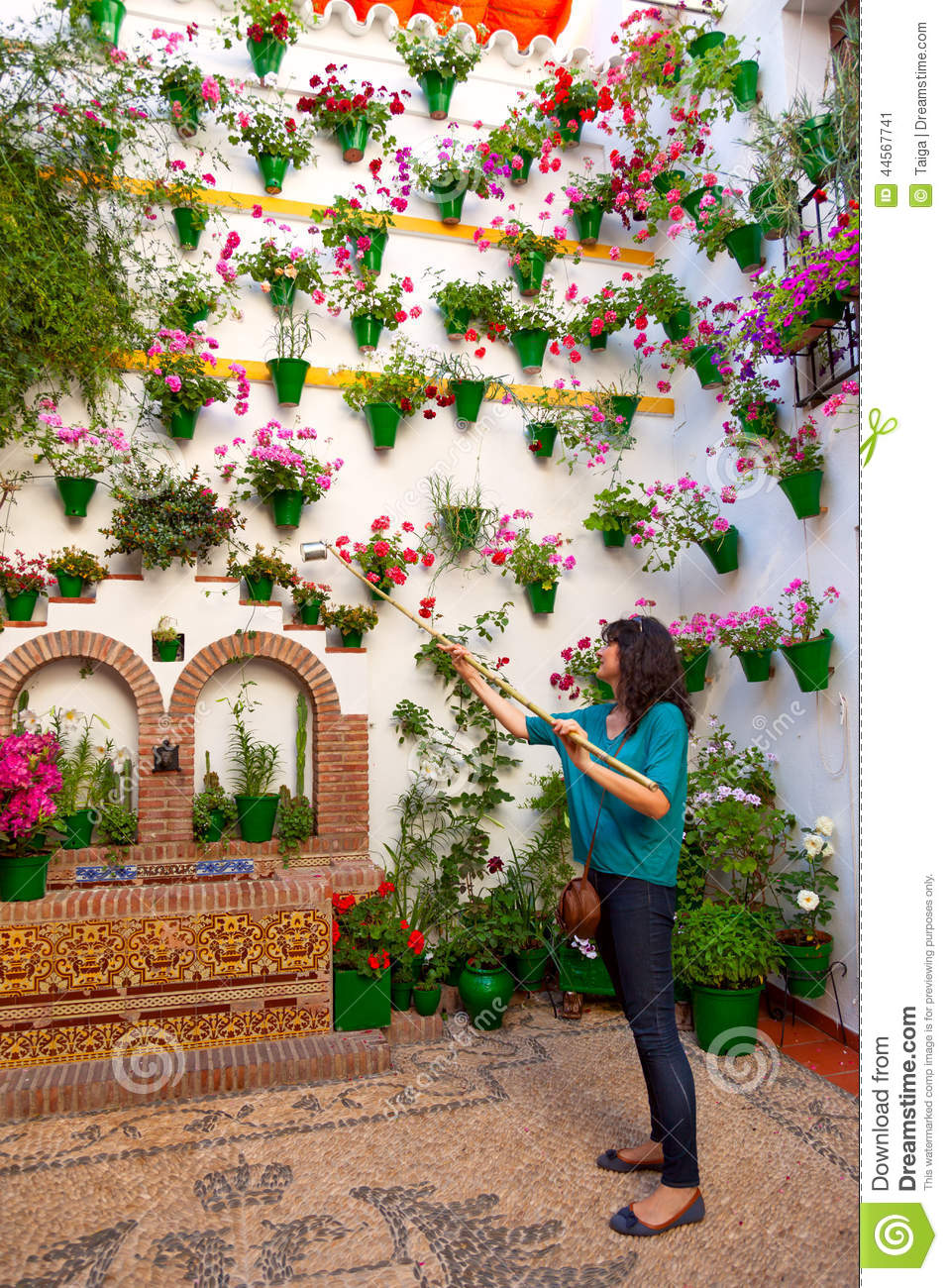 Woman is watering the flowers on wall cordoba patio fest for Fotos de patios