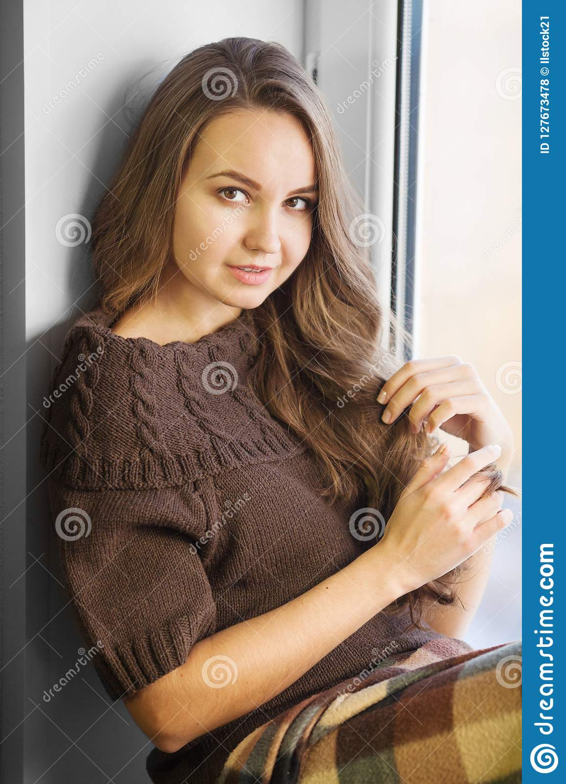 Brown Haired Woman Sitting On Window Sill And Posing Stock Photo