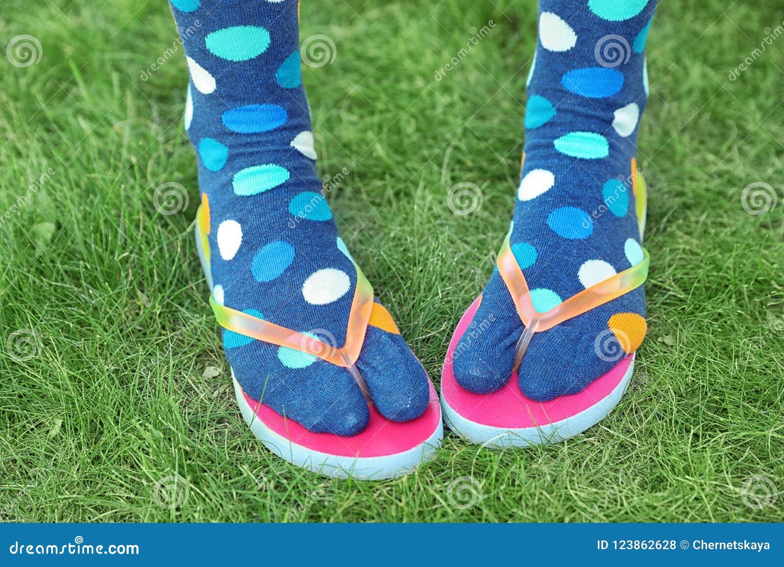 Woman wearing bright socks with flip-flops standing