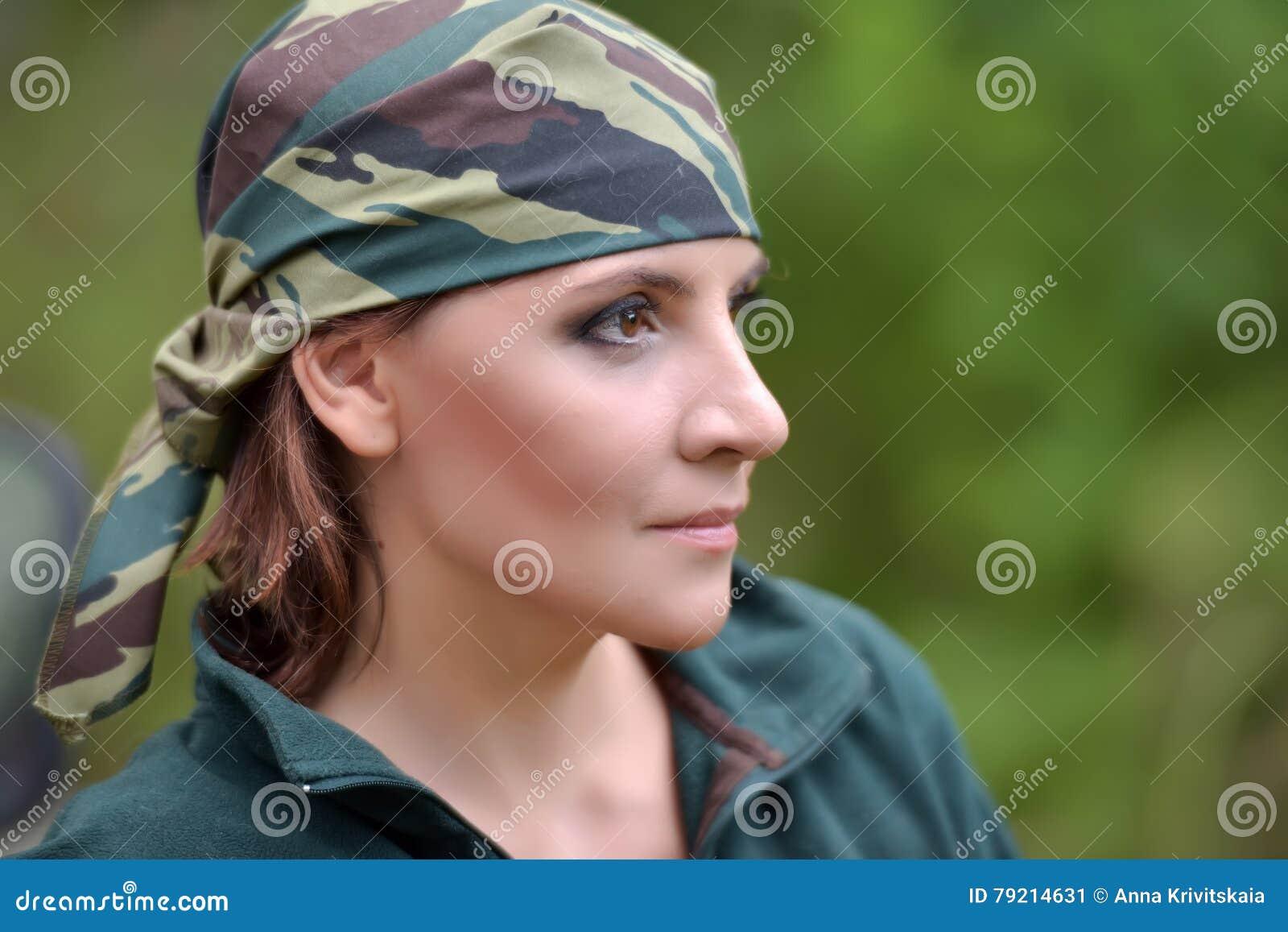Woman wearing camouflage bandana against the backdrop of UAZ
