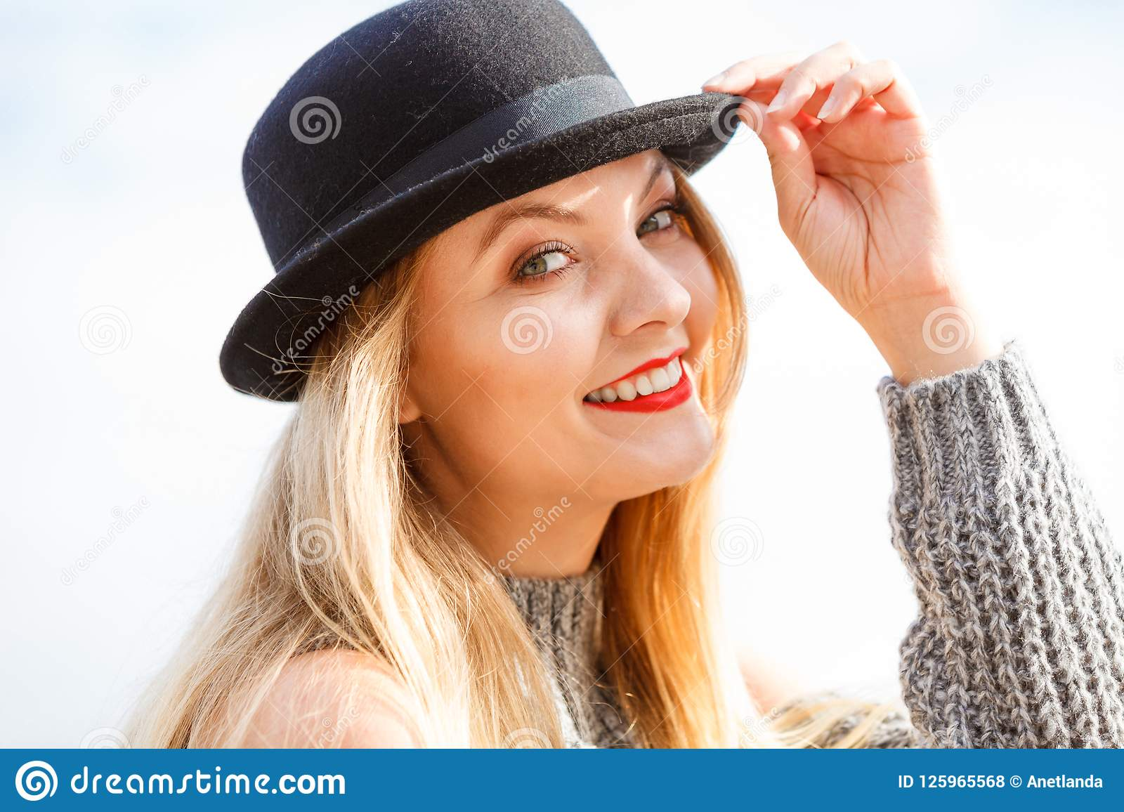 795bebd9 Beautiful young blonde woman wearing fedora hat and sweater jumper posing  on sky background.