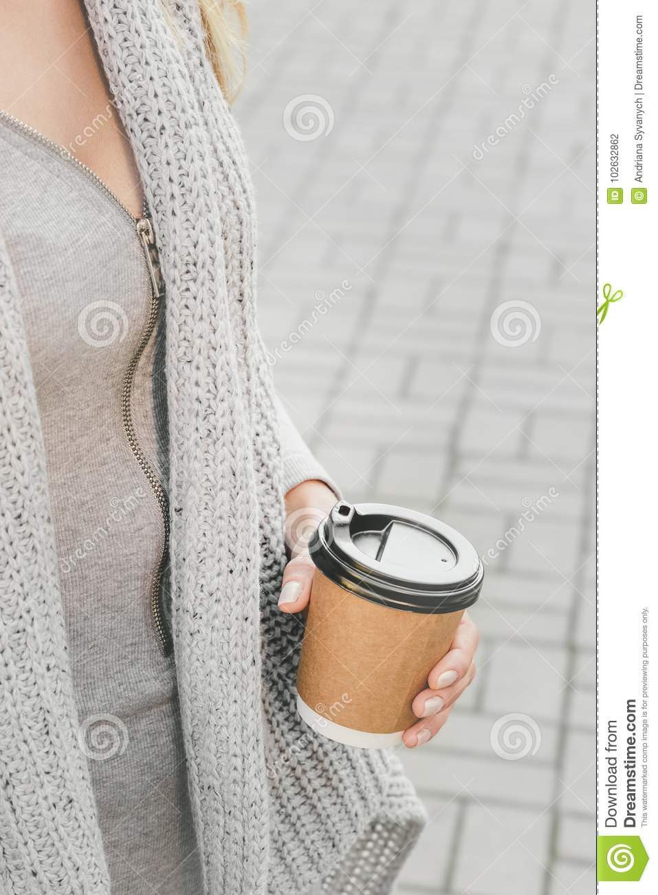 b3212ff6d1f Woman wearing grey cardigan holding coffee-to-go in paper cup on the city  street