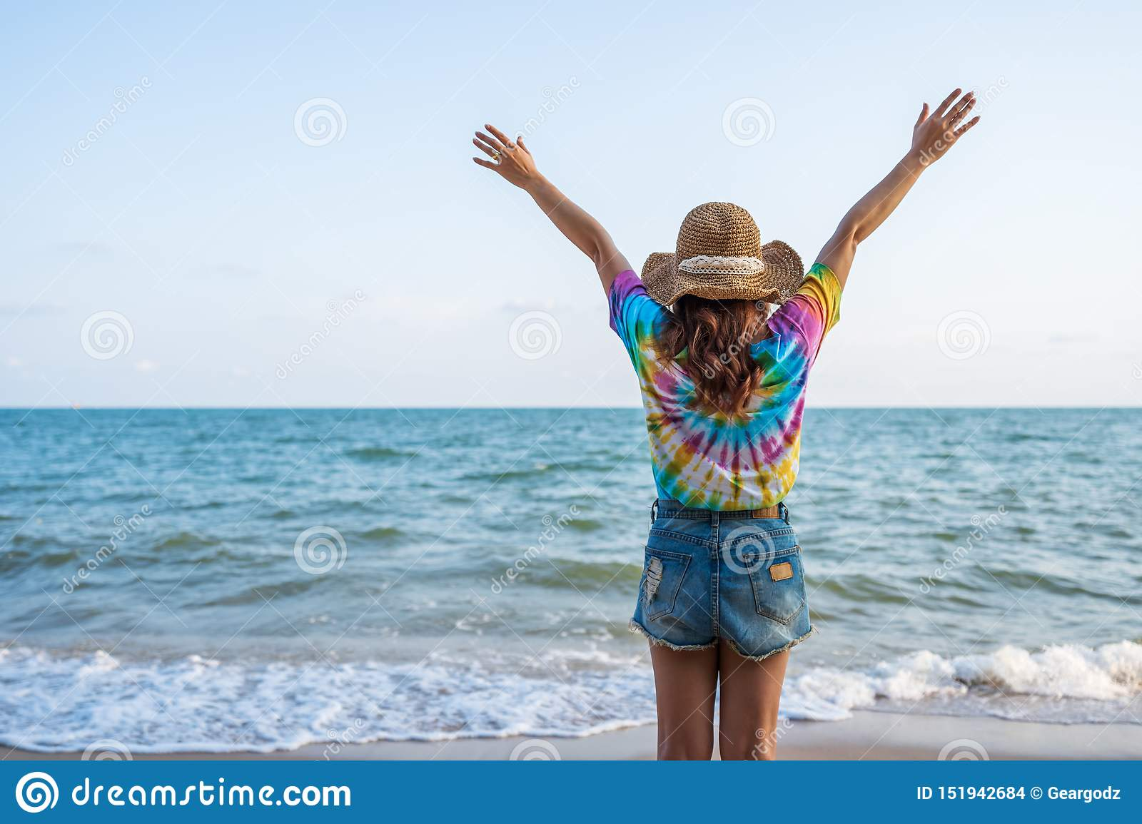 Woman wearing hat with arms raised standing on sea beach