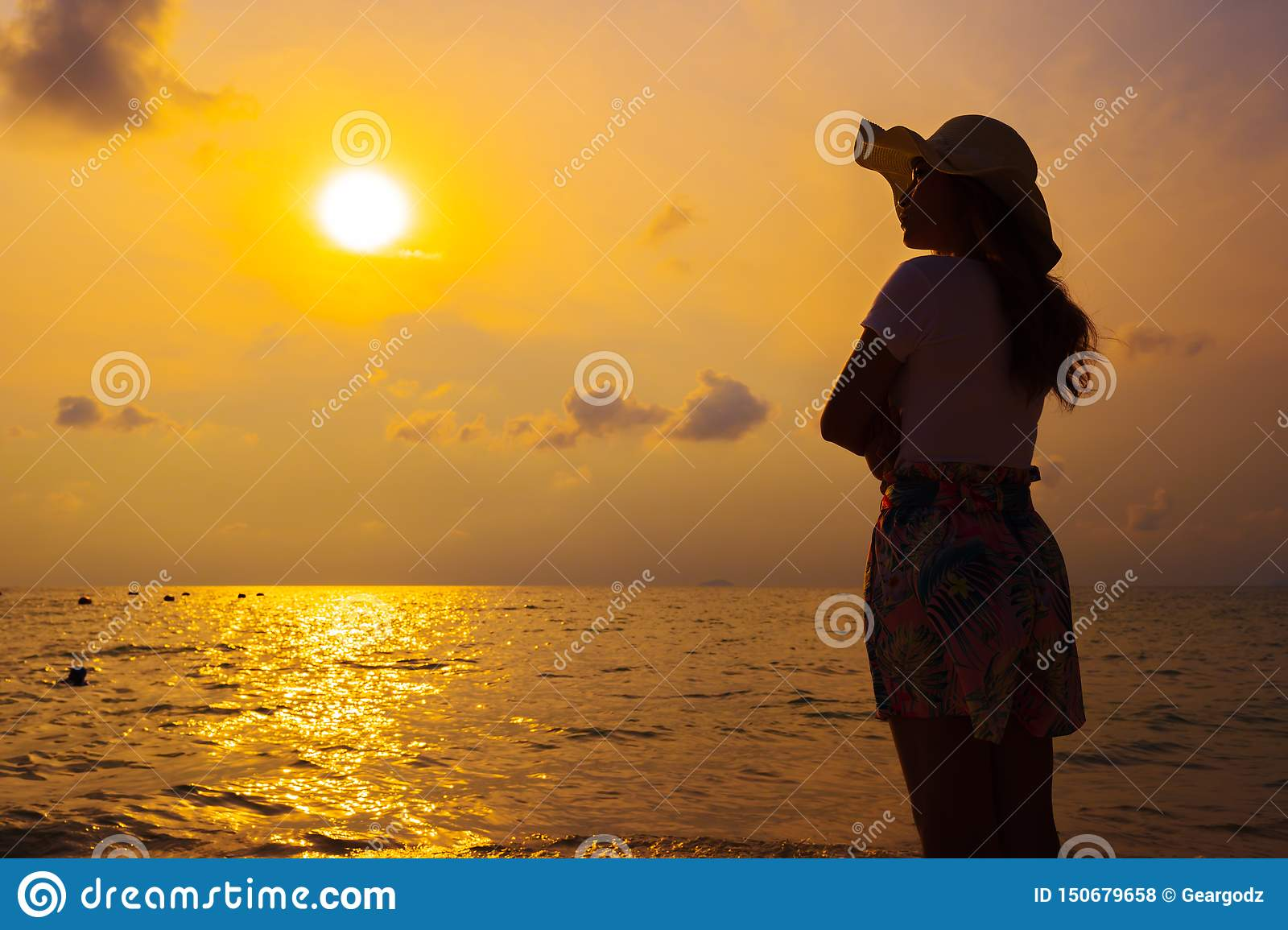 Woman wearing hat standing on sea beach at sunset