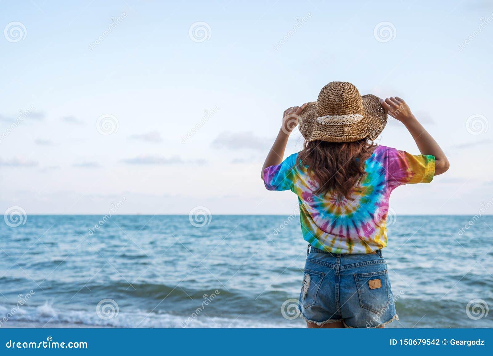 Woman wearing hat standing on sea beach