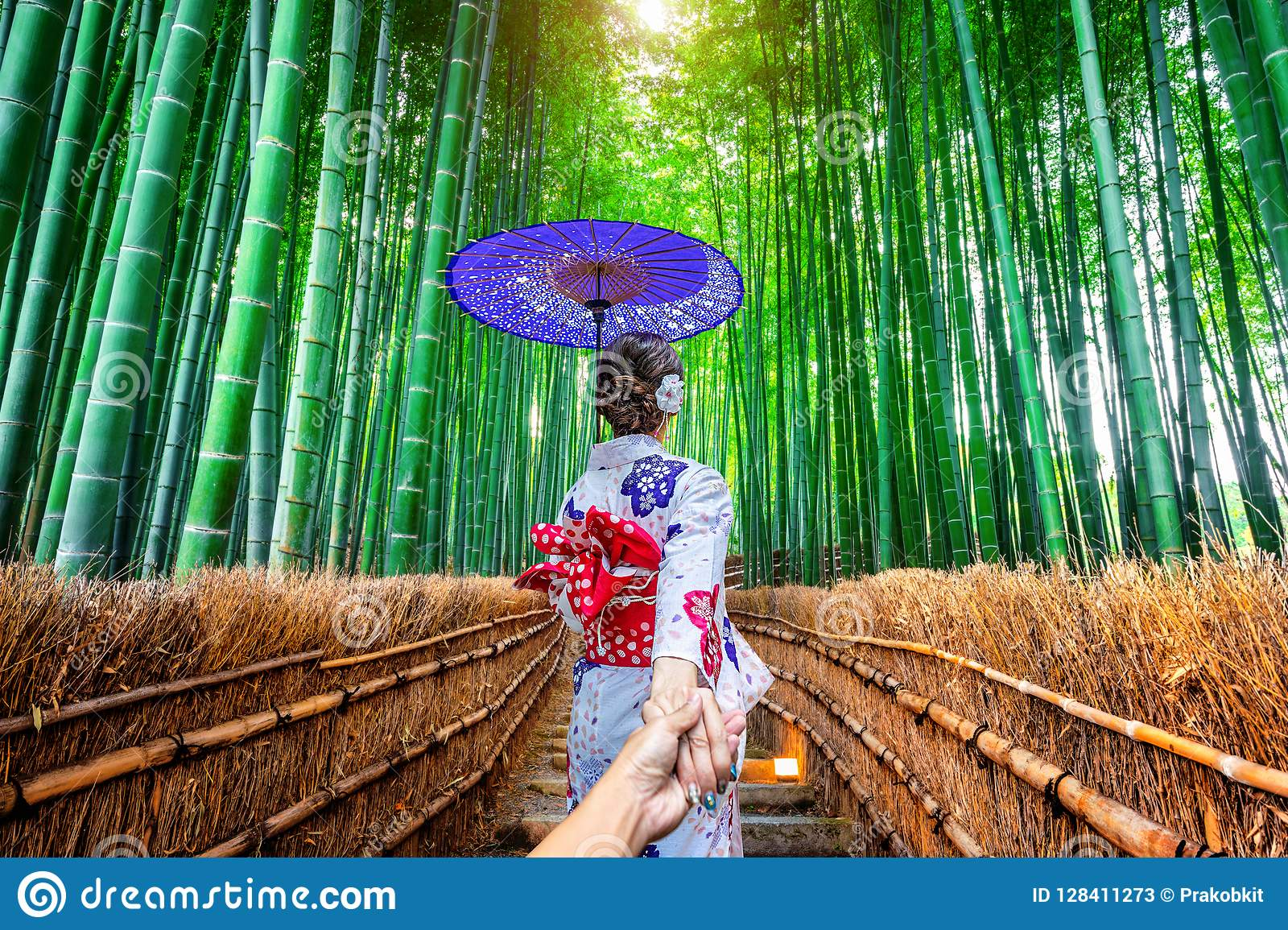 Woman wearing japanese traditional kimono holding man`s hand and leading him to Bamboo Forest in Kyoto, Japan
