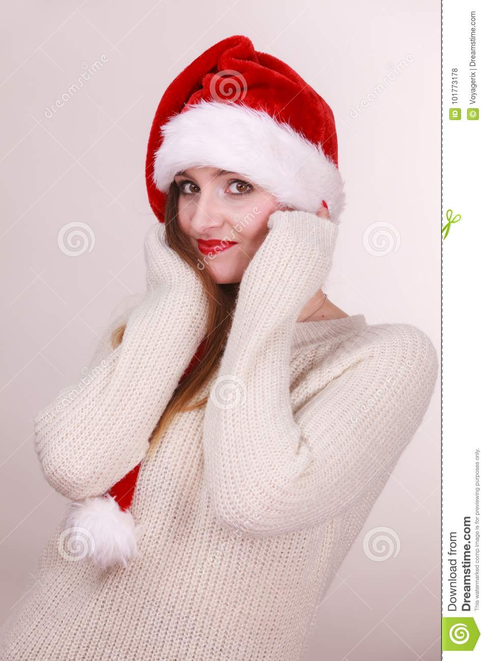 4efe53fc20e Christmas time. Young lady wearing santa claus hat and warm woolen sweater.  Celebration holiday concept.