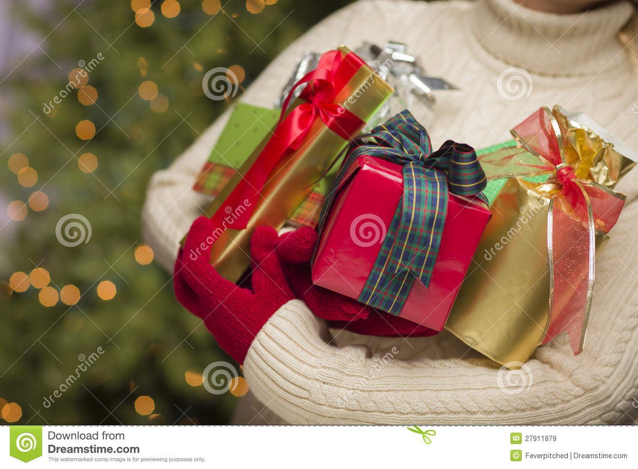 Woman wearing seasonal red mittens holding christmas gifts royalty