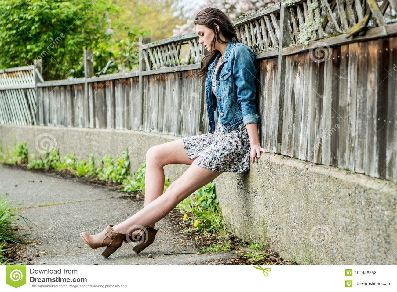 9c0c1ad4449 A young woman sitting along a wooden fence in a urban or suburban setting  wearing a short bohemian style floral dress with a denim jacket.