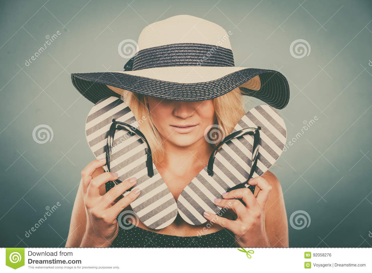 51be40e642bbd2 Summer trendy fashionable outfit ideas concept. Blonde unrecognizable  mysterious woman wearing blue dress and sun hat holding flip flops.