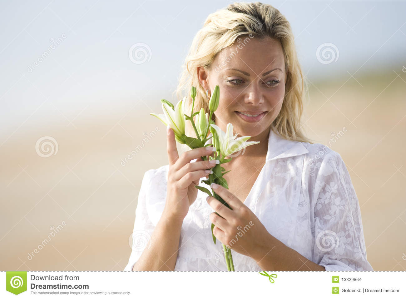 Woman wearing white on beach holding flower