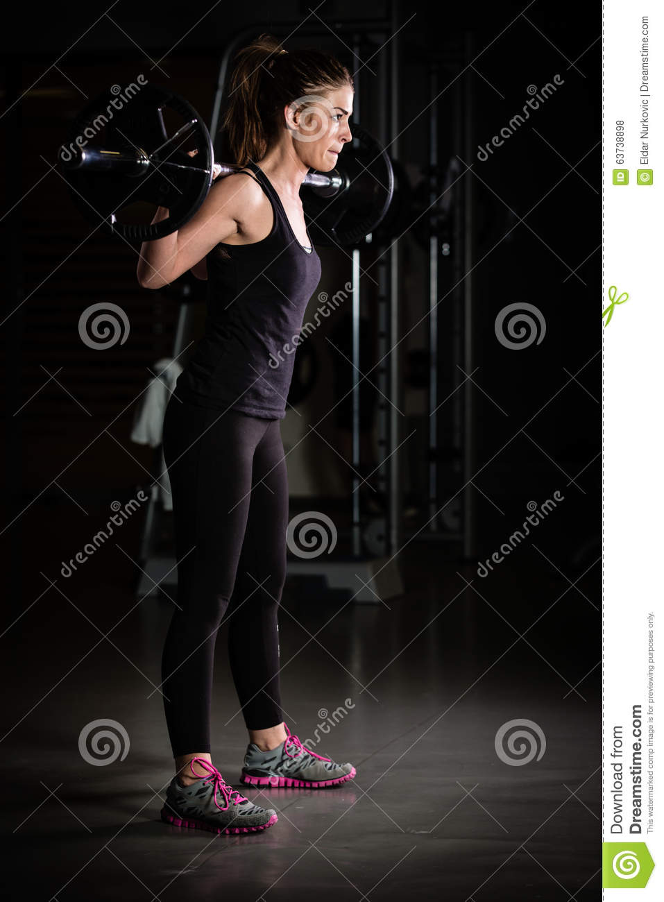 Woman weight training at gym.Devoted body builder girl lifting weights in gym and doing squats low key photo