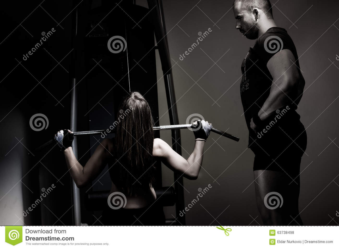 Woman weight training at gym.Exercising on pull down weight machine/