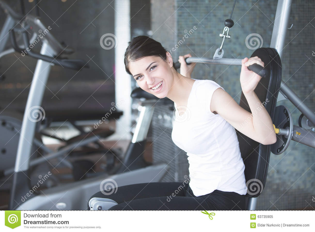 Woman weight training at gym.Exercising on pull down weight machine.Woman doing pull-ups exercising lifting dumbbells.