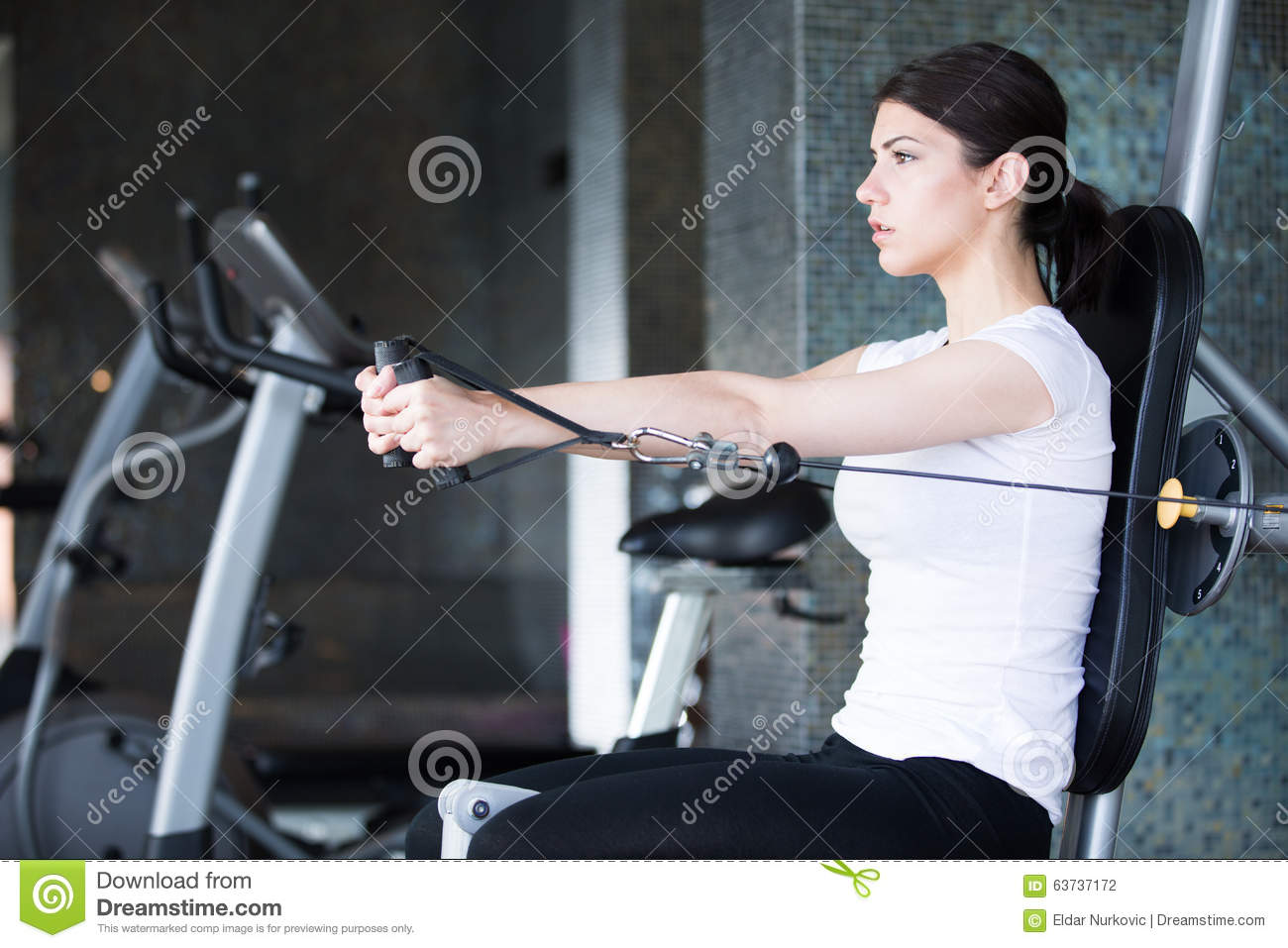 Woman weight training at gym. Exercising on pull down weight machine. Woman doing pull-ups exercising lifting dumbbells.