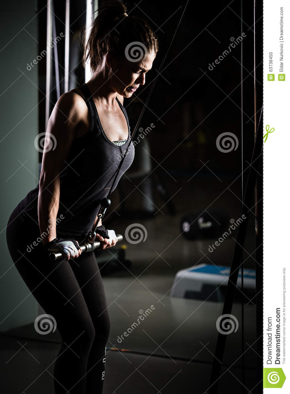 Woman weight training at gym.Exercising on pull down weight machine.Woman doing pull-ups exercising lifting dumbbells