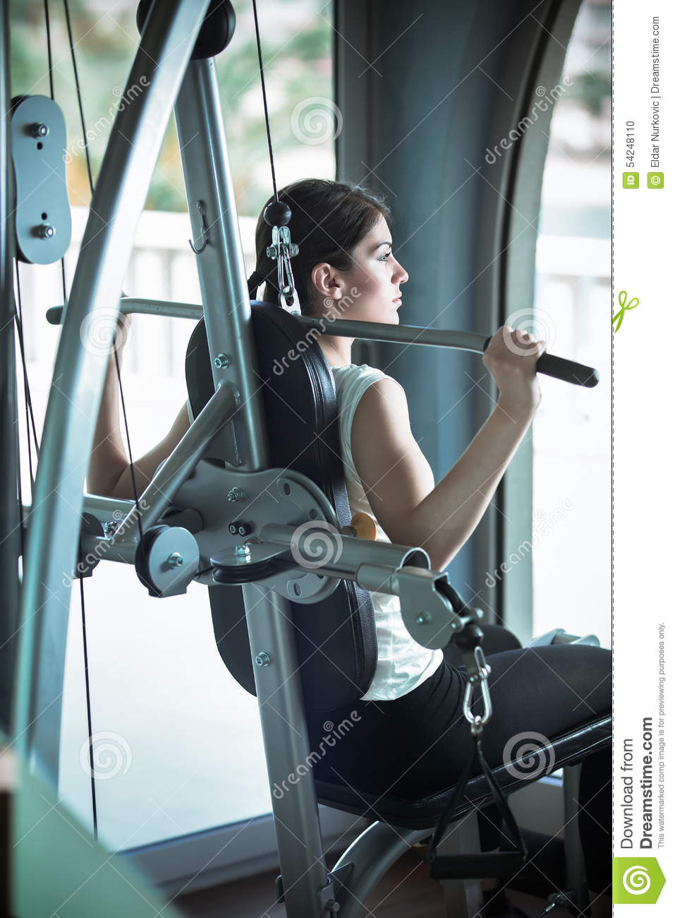 Woman weight training at gym.Exercising on pull down weight machine.Woman doing pull-ups exercising lifting dumbbells.Cardio and
