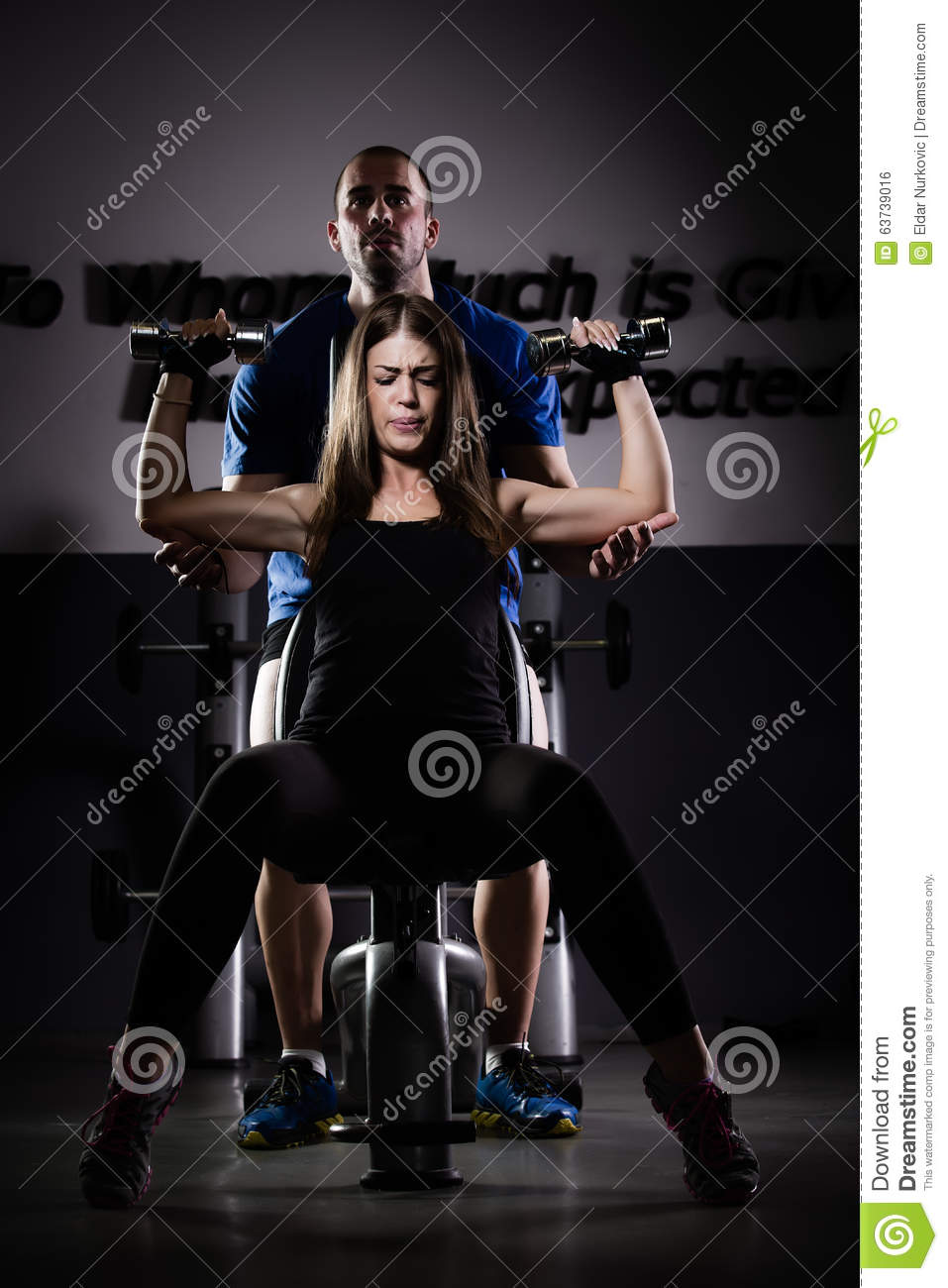 Woman weight training at gym.Woman doing pull-ups exercising lifting dumbbells