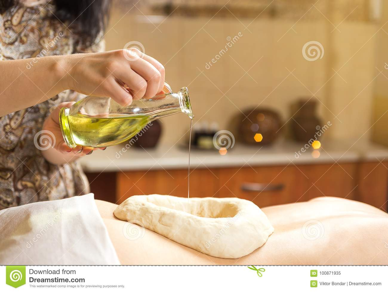 woman in wellness spa having aroma therapy massage with essential oil,Woman enjoying a Ayurveda oil massage treatment in