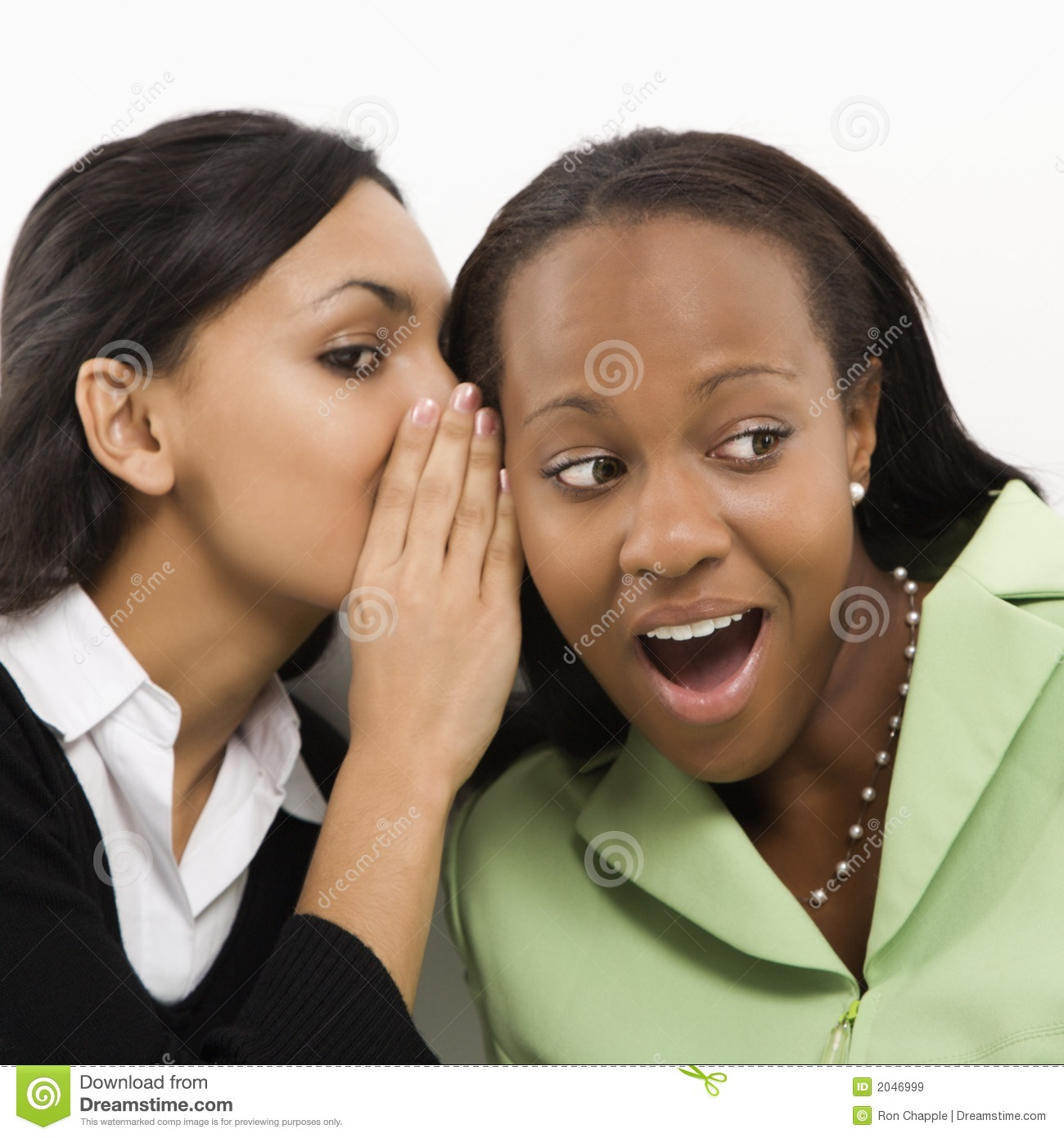 ... adult woman whispering in ear of mid-adult African-American woman
