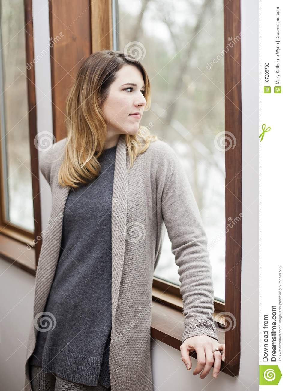 Woman with winter depression looking out window