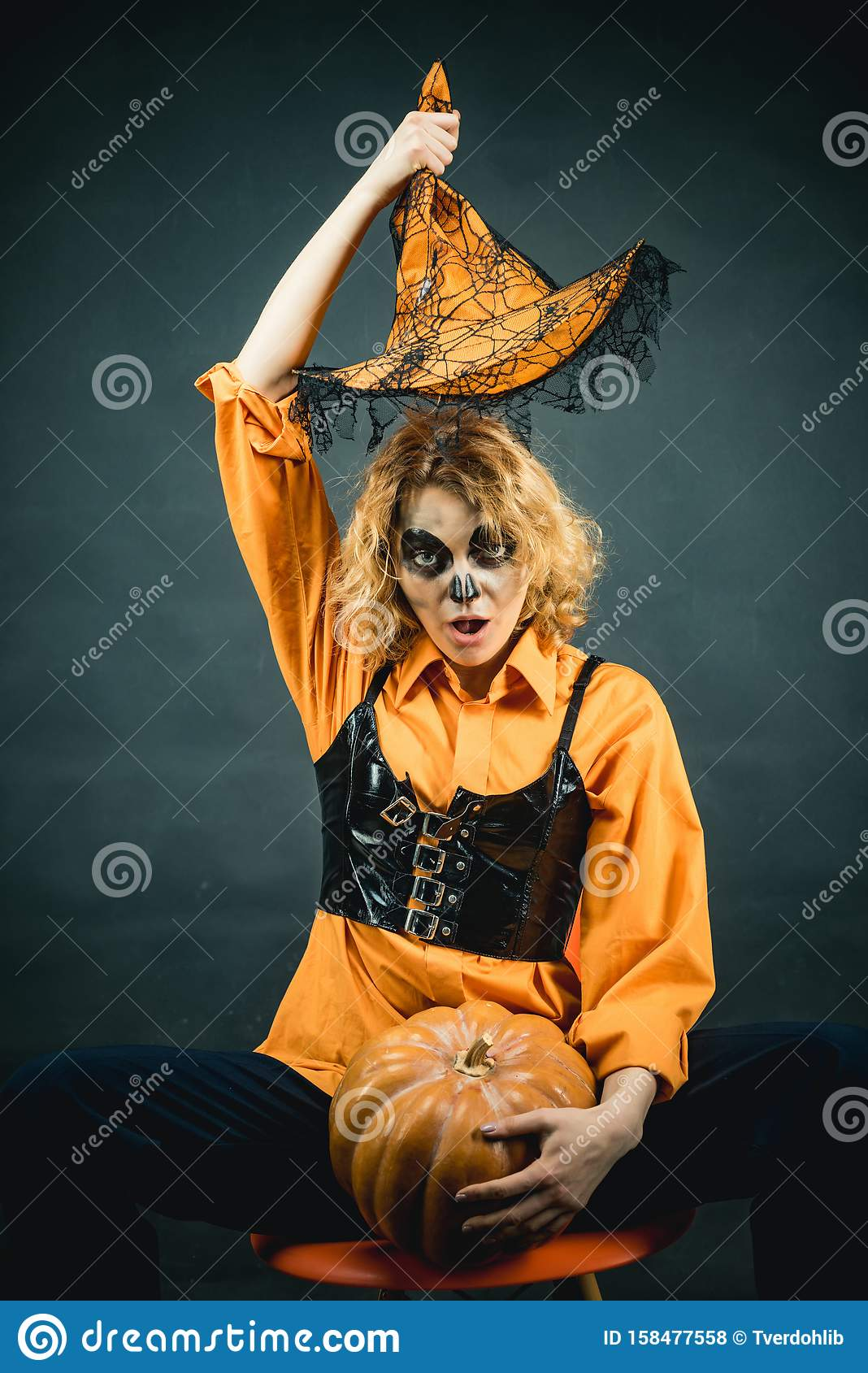 Woman witch with pumpkin. Young woman with witch hat dressed as vampire for Halloween party. Witch in magic hat.