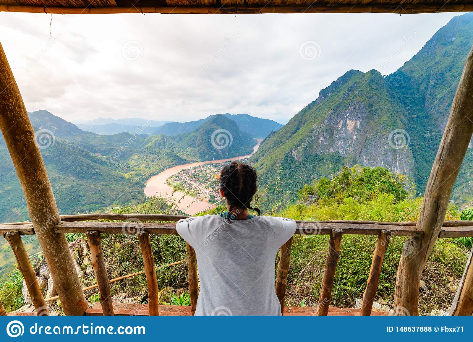 Woman on wooden balcony conquering mountain top at Nong Khiaw Nam Ou River valley Laos mature people traveling millenials concept