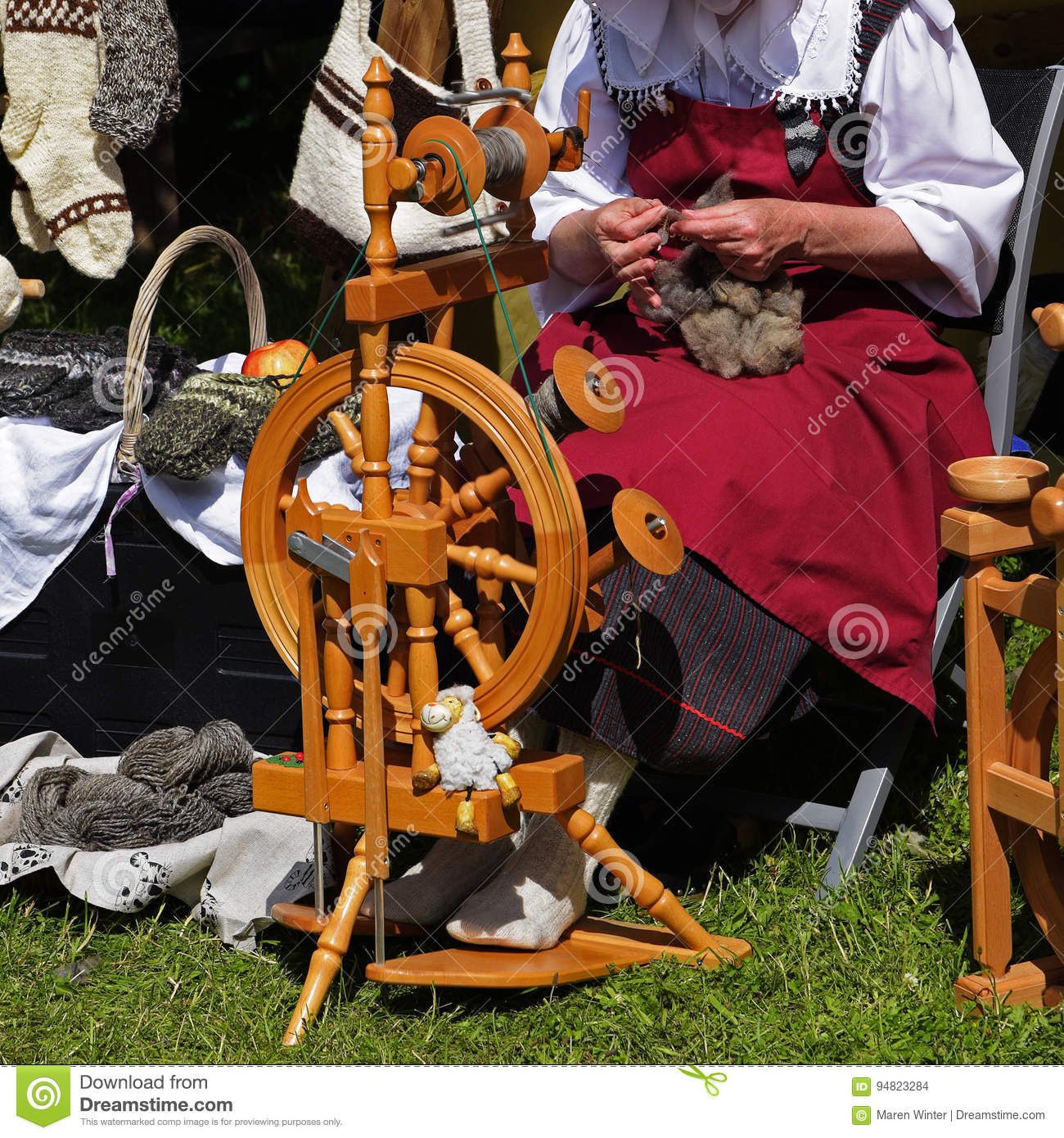 Woman with wool at the traditional spinning wheel on an medieval