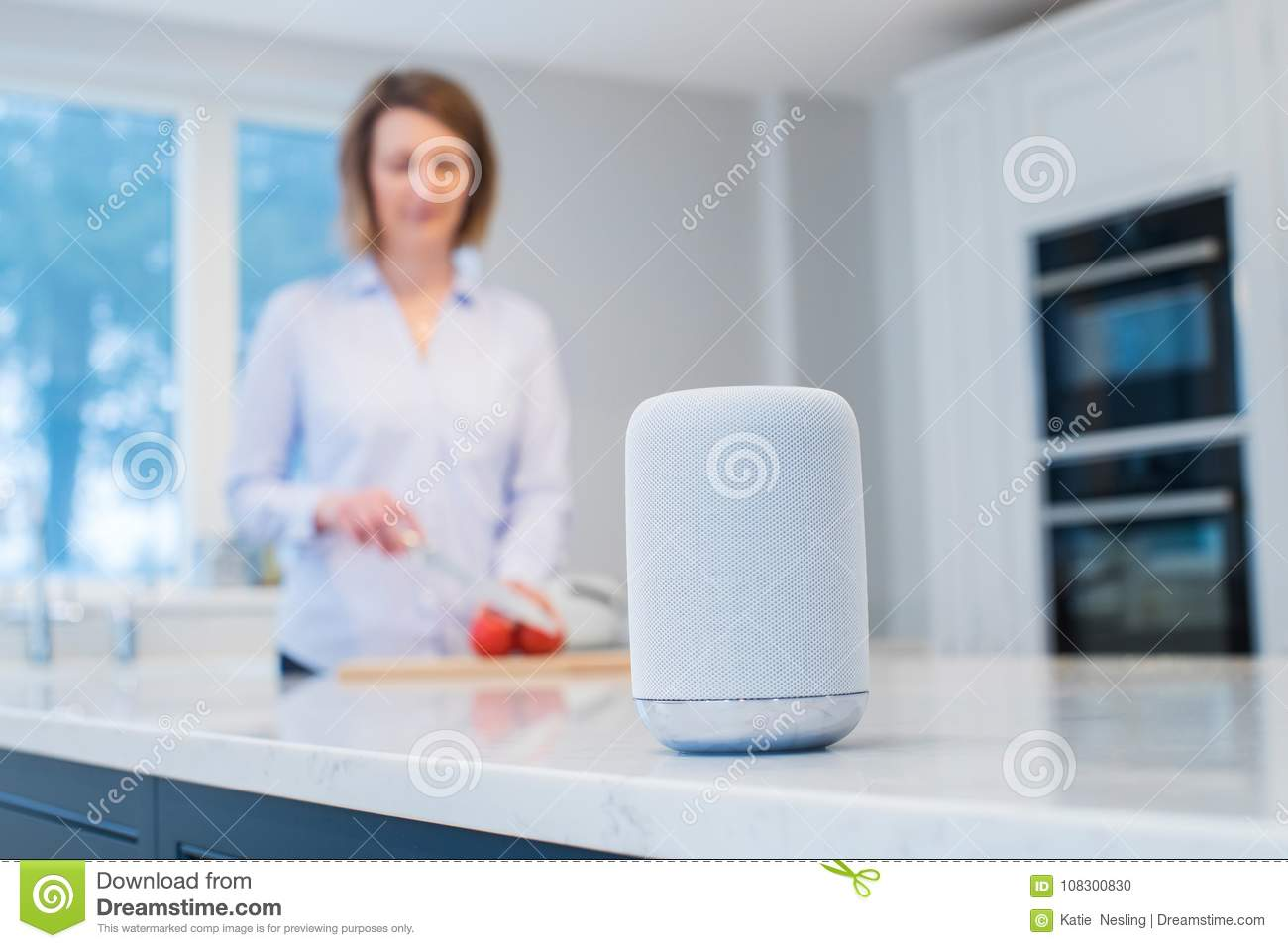 Woman Working In Kitchen With Smart Speaker In Foreground Stock ...