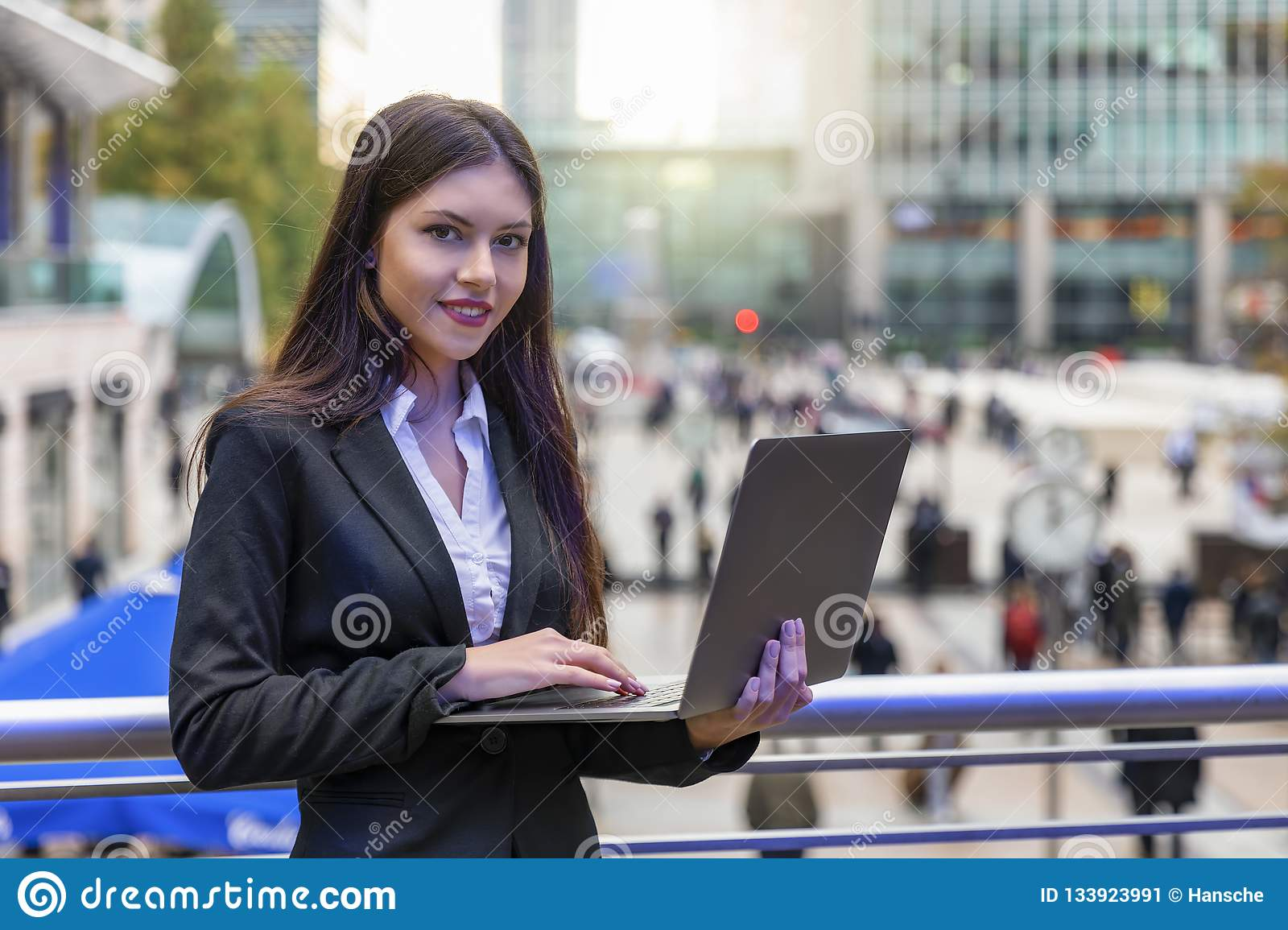 Woman working on a laptop outdoors in Canary Wharf, UK