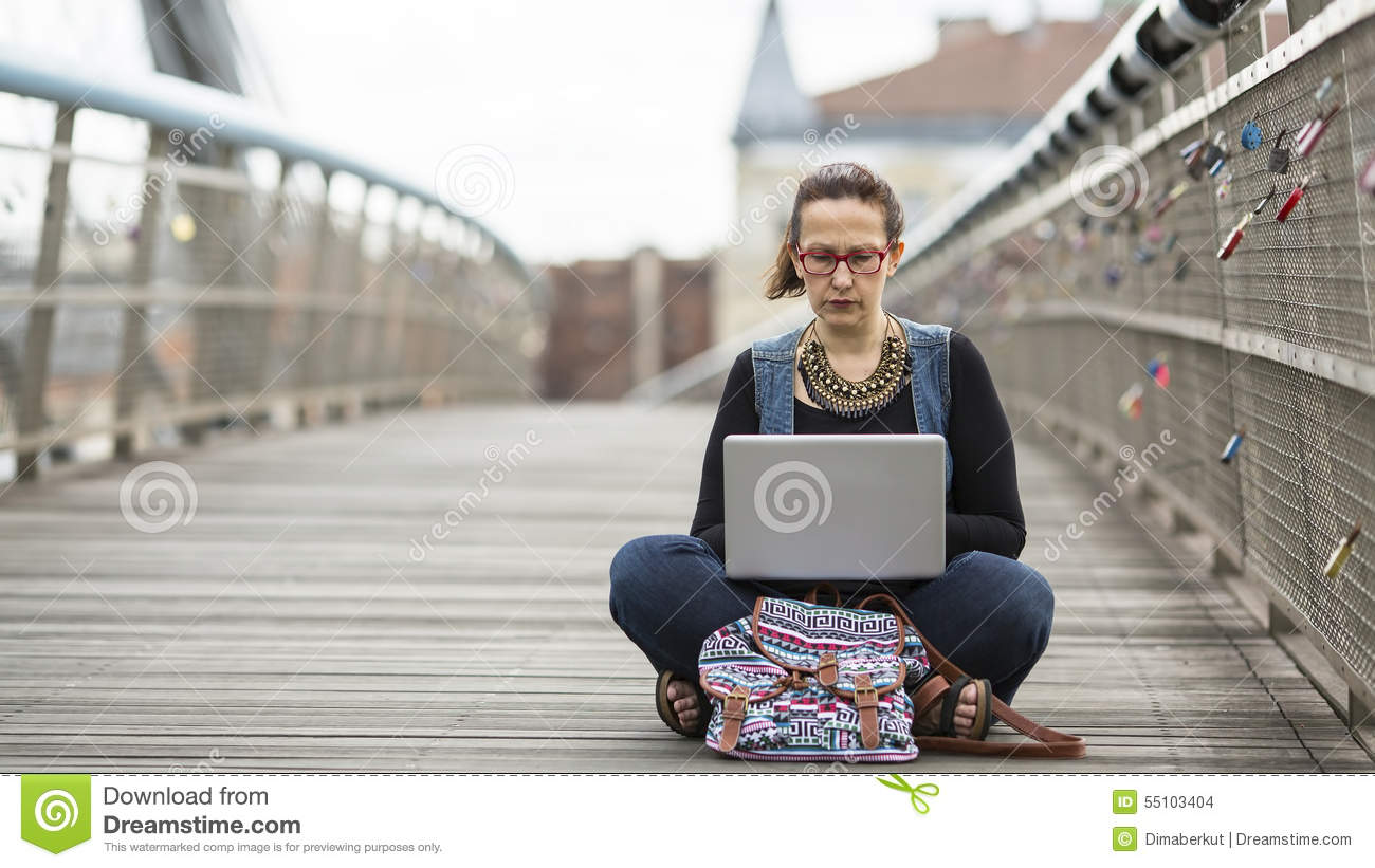 woman working on laptop while sitting on the street. The concept of working Freelancer or Blogger.