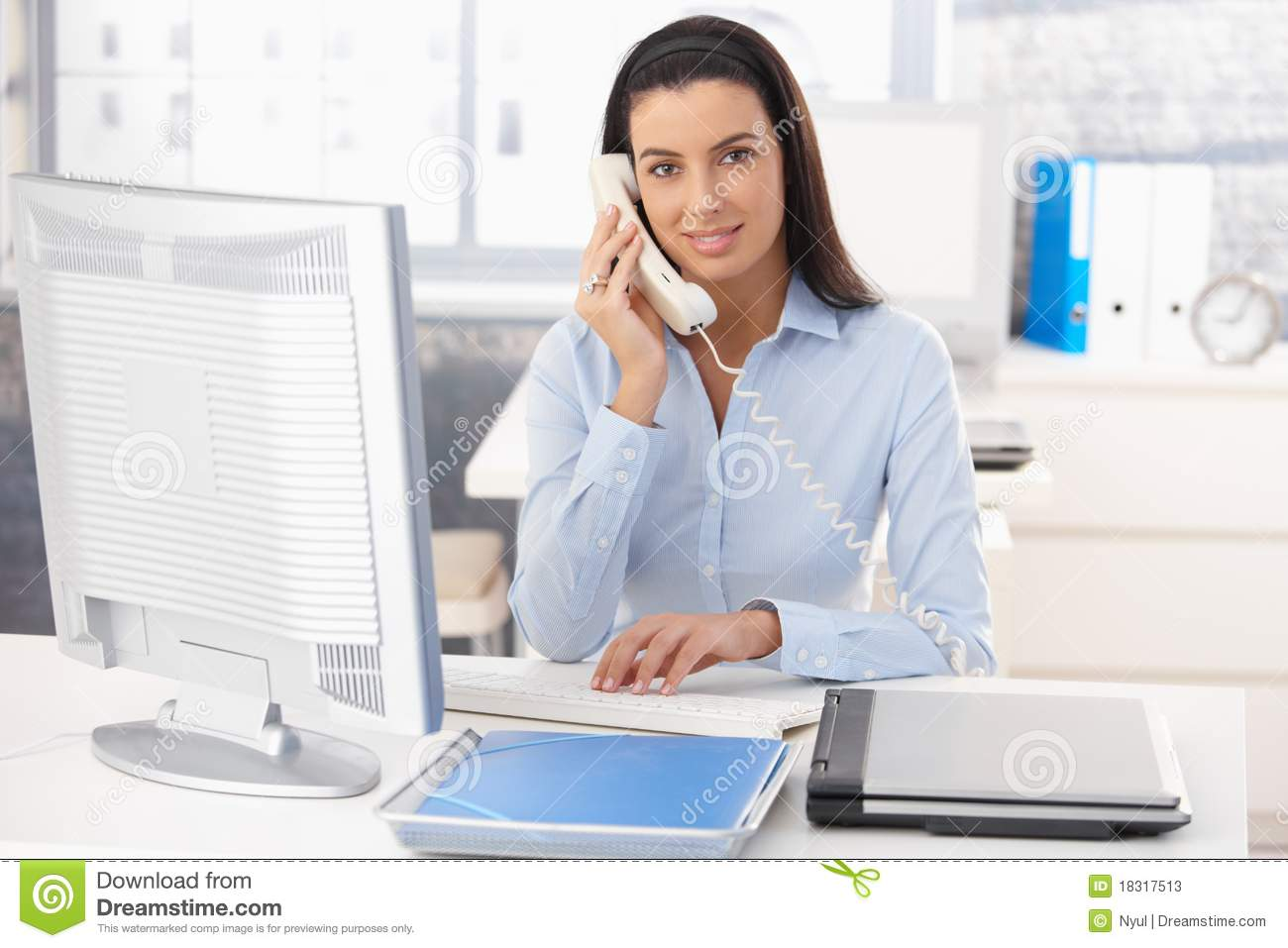 Portrait of smiling woman working in office, using computer and ...