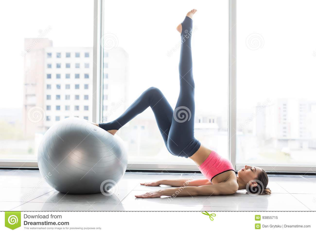 Woman working out with exercise ball in gym. Pilates woman doing exercises in the gym workout room with fitness ball. Fitness woma
