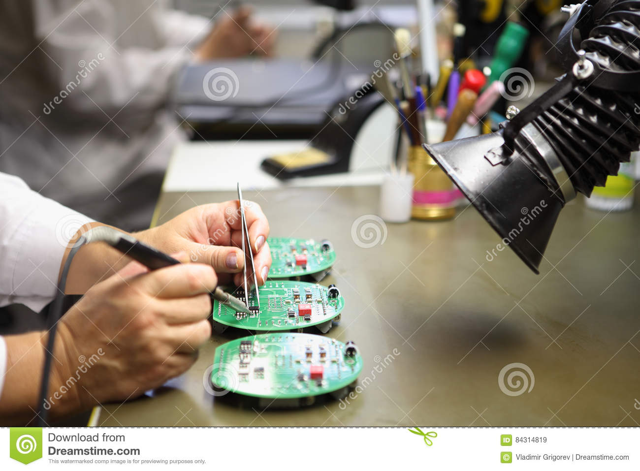 Woman works in manual assembly of electronic printed circuit b