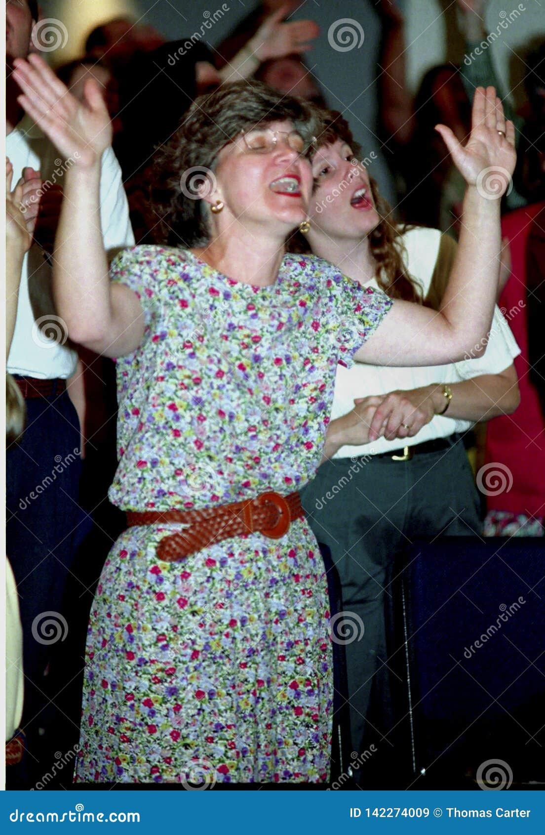 Woman in prais e at a Pcharismatic church service r