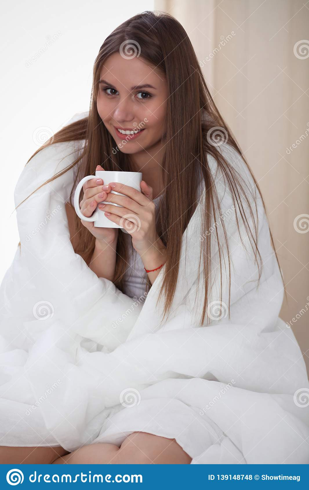 Woman wrapped in a blanket and holds a mug after wake up, entering a day happy and relaxed after good night sleep. Sweet